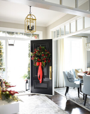 Gorgeous black front door with 30 inch christmas wreath with red bow and berries