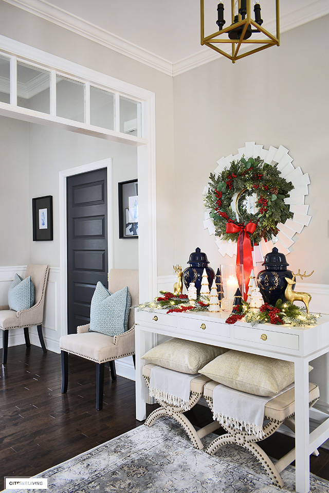 This entryway is decorating for the Holidays with beautiful greenery accented with red berries, console table with a symmetrical display of ginger jars and accessories.