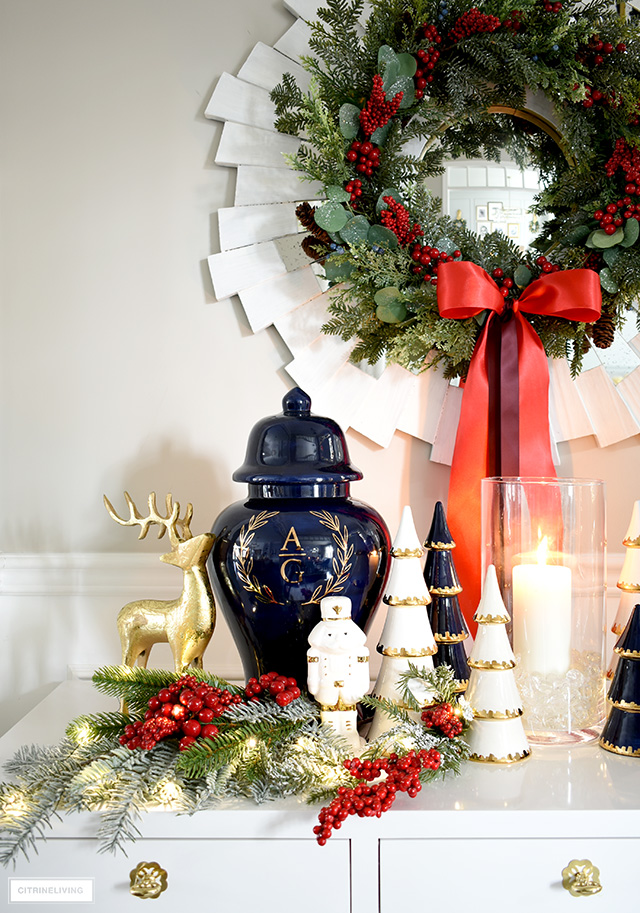 A beautiful Holiday display on a console table with a ginger jar, ceramic Christmas trees, nutcrackers and greenery.
