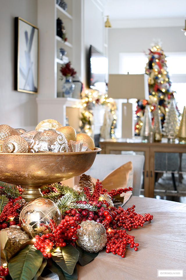 A pretty Christmas centerpiece with ornaments and red berries with magnolia leaves sits on a dining room table, with a view into a living room with garland and Christmas tree.