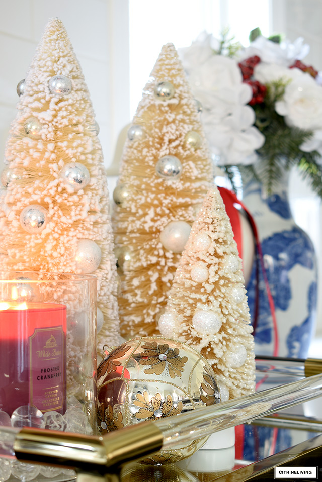 Pretty bottle brush trees syled on a tray with a scented candle and ornament.