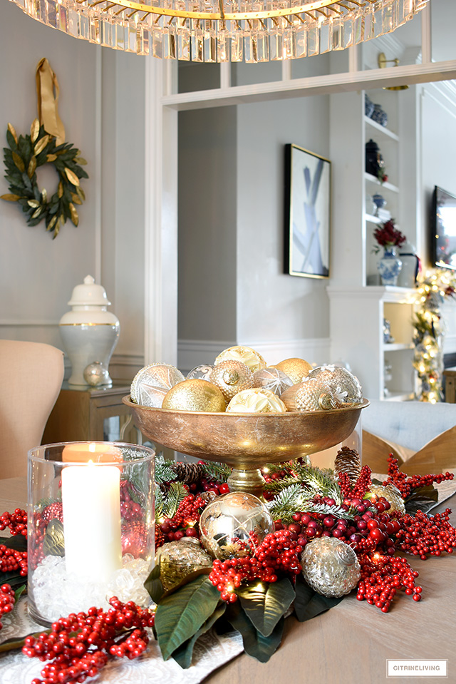 Gold footed decorative bowl filled with silver and gold Christmas ornaments, arranged with a red berry and magnolia centerpiece.