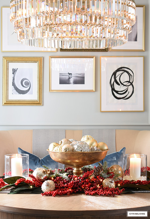 Christmas centerpiece with red berries, magnolia leaves, candles and pretty ornaments.