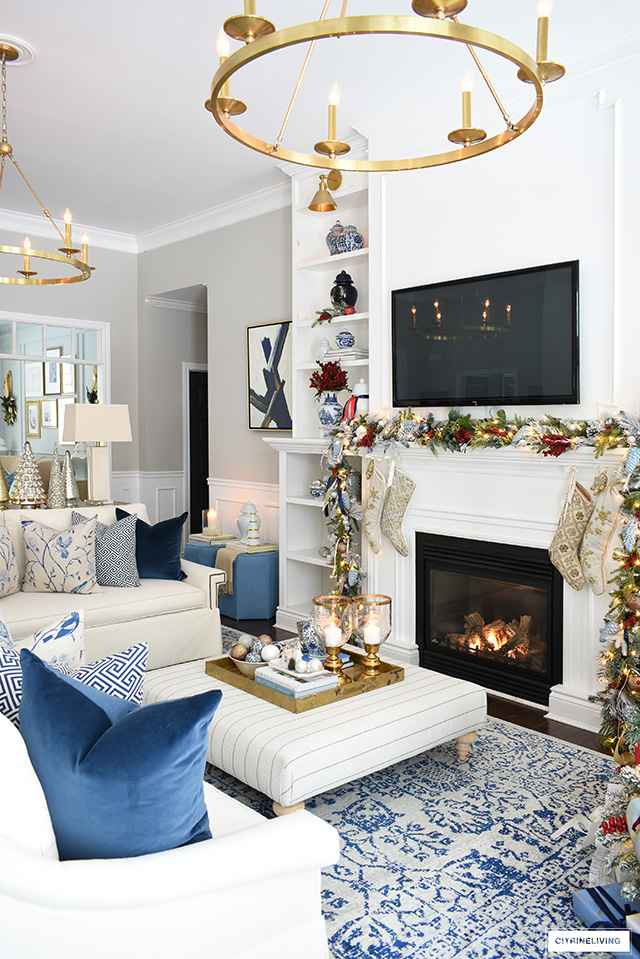 Living room decorated for Christmas with blue, white, red and gold.