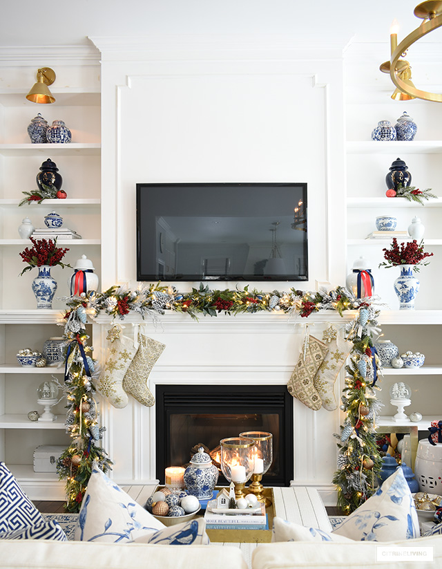 Bookshelves and mantel styled with decorated Christmas garland and stockings.