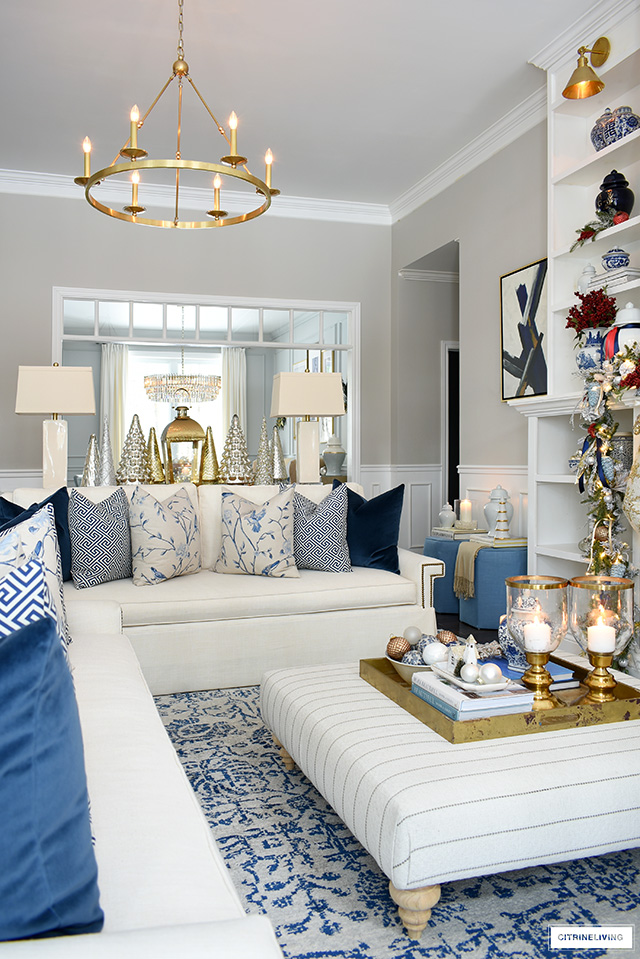 Christmas living room decor in blue and white with red accents.