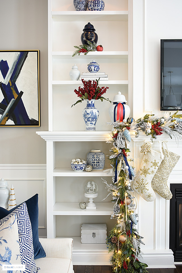 Living room bookshelves styled for Christmas with blue and white chinoiserie and red accents.