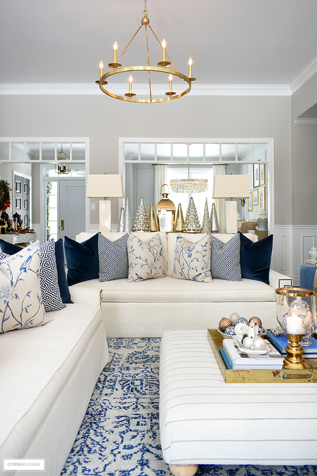 Christmas living room with beautiful blue and white throw pillows, gold and silver accents.