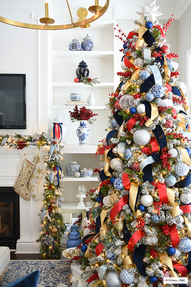 Red and blue Christmas tree with gold accents. Bookshelves decorated with blue and white ginger jars and vases.