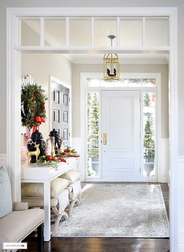 A view into a Christmas decorated entryway with a white console table, gold lantern style light and vintage inspired rug.