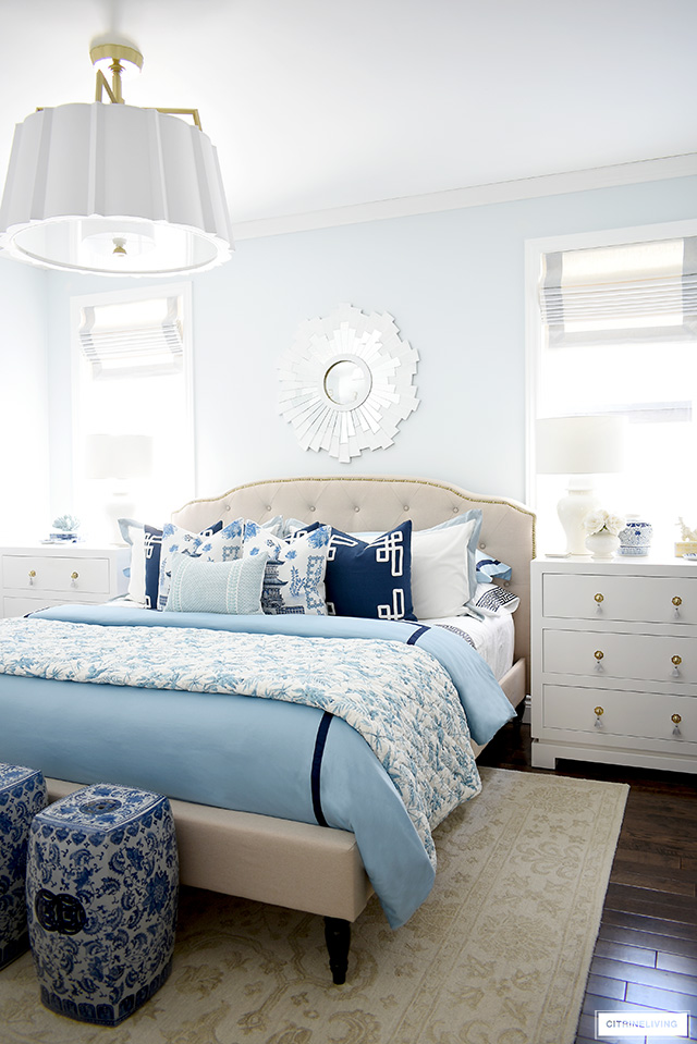 Gorgeous master bedroom decorated for spring in blue and white chinoiserie chic style, tailored roman shades, white dressers and statement lighting.