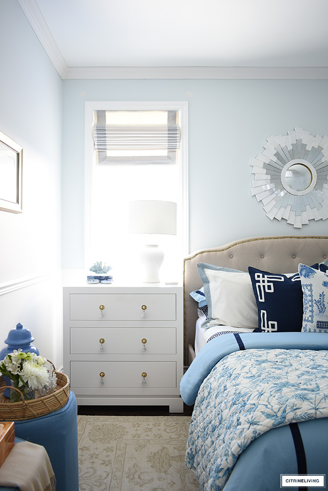 Spring bedroom decorated with blue and white bedding, crisp roman shades and white lacquered dressers.