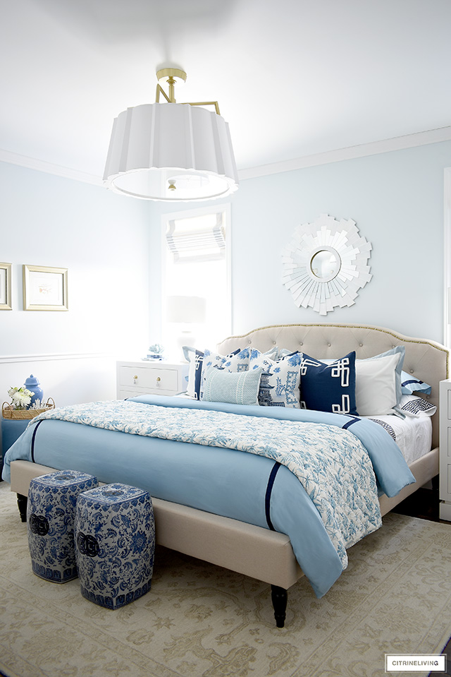 Master bedroom decorated for spring with beautiful layers of blue bedding and throw pillows.