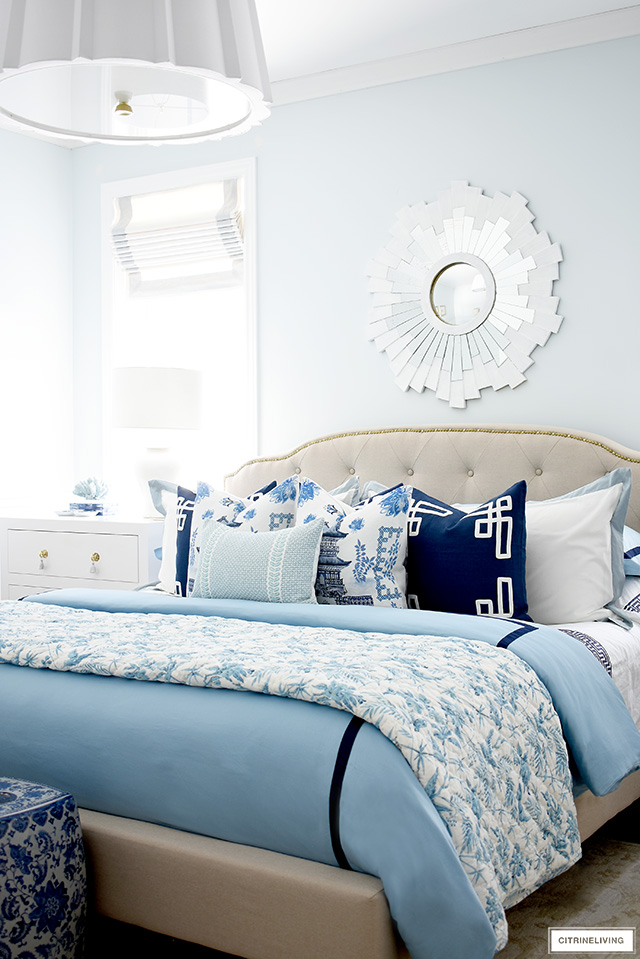 Gorgeous and luxurious bed styled with layers of blue and white bedding and throw pillows.