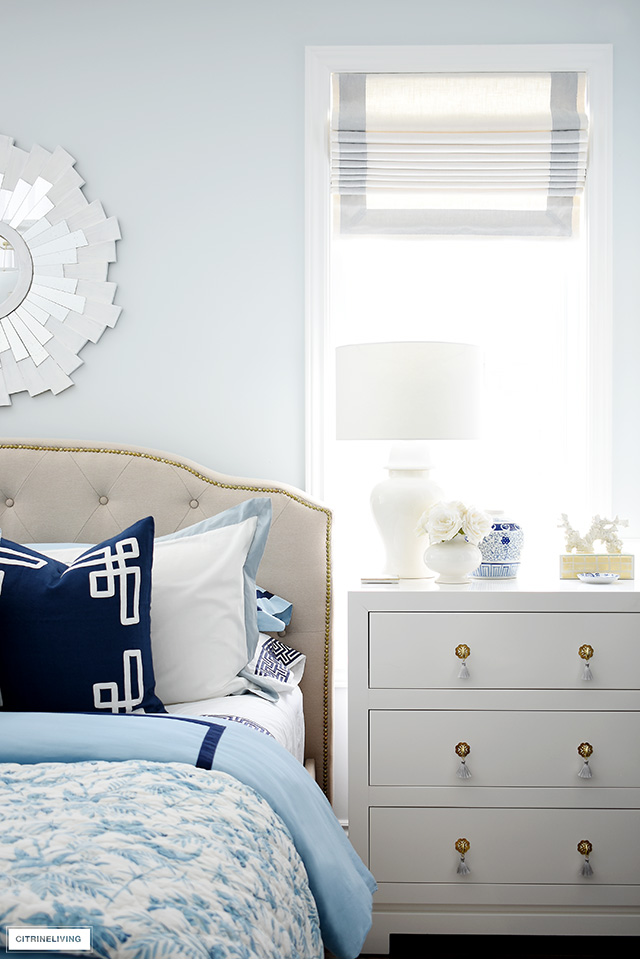 Spring bedroom decor with elegant and tailored roman shades, blue and white bedding and accents.