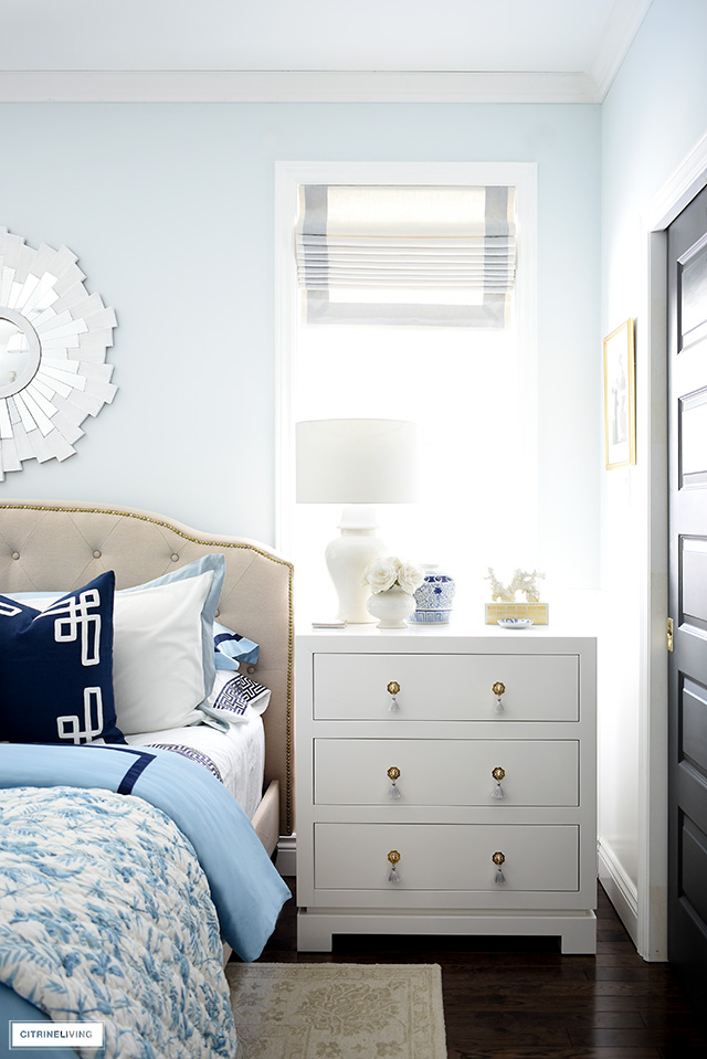 Blue and white decorated bedroom for spring with white dressers, ginger jar lamps and roman shades.
