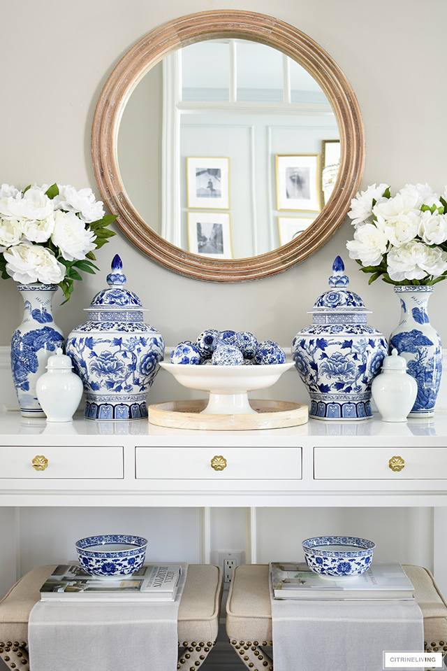 White entryway table decorated with a symmetrical display of blue and white jars and vases, faux peonies and a round wooden mirror.