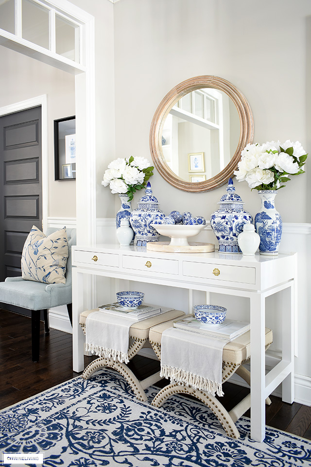 Entryway decor with a white lacquered console table, styled with blue and white chinoiserie, faux florals and wooden touches.