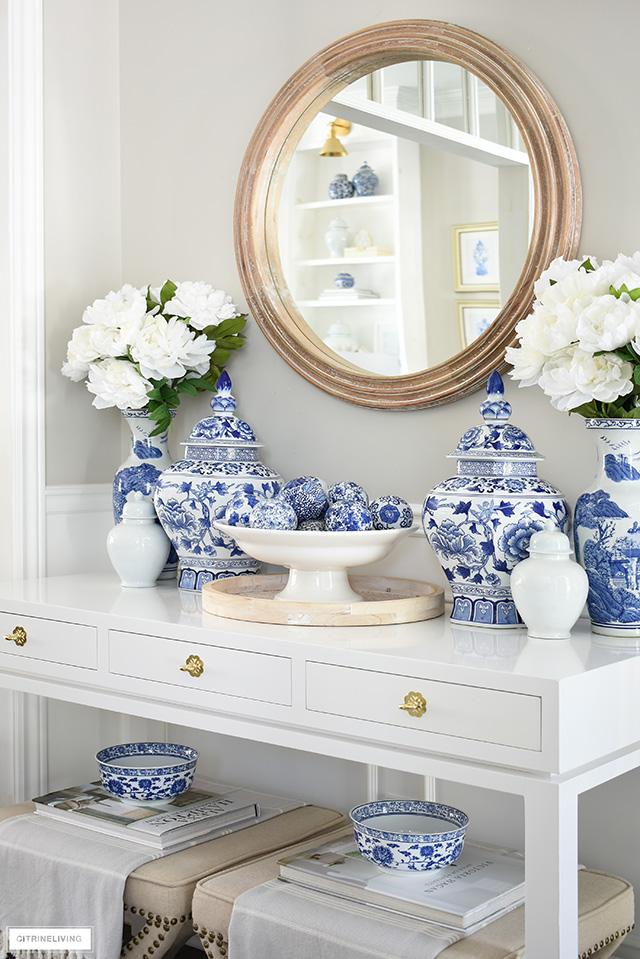 Spring decorated table vignette with blue and white chinoiserie, faux peonies and a round wooden mirror.