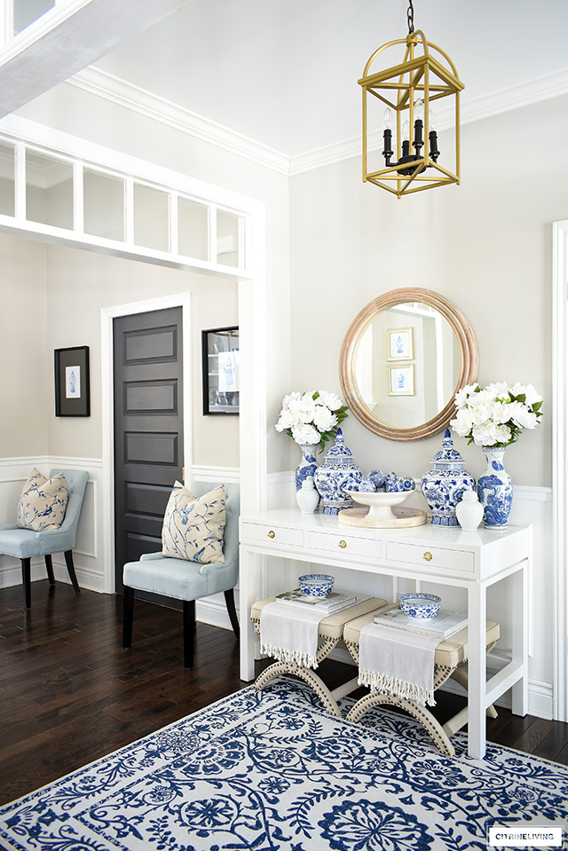 Entryway decorating for spring with vibrant blue and white, faux florals and natural wood accents.