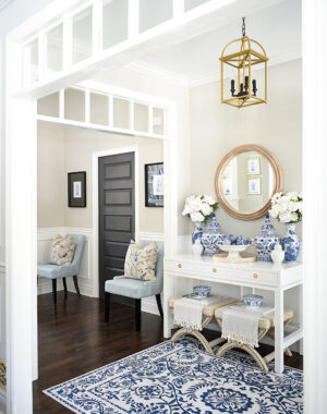 Spring entryway deocrated in layers of blue and white chinoiserie ginger jars, faux peonies and a blue and white print rug.