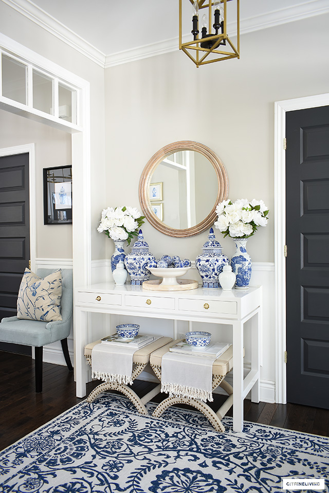 Bright and elegant entryway decor with a white console table, blue and white ginger jars, vases, bowls and decorative balls. Accented with natural wood touches.