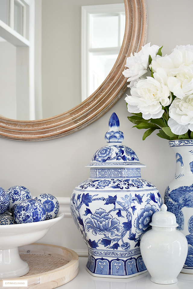 Blue and white ginger jar and vases with faux peonies styled on a white table.