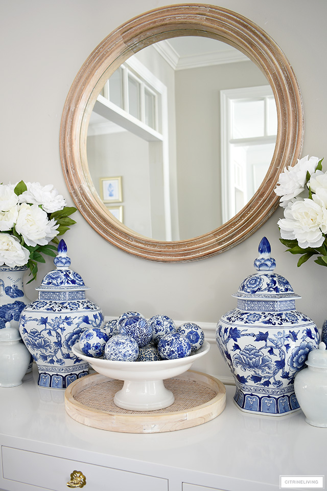 A tabletop vignette with blue and white decor and a round wooden mirror.