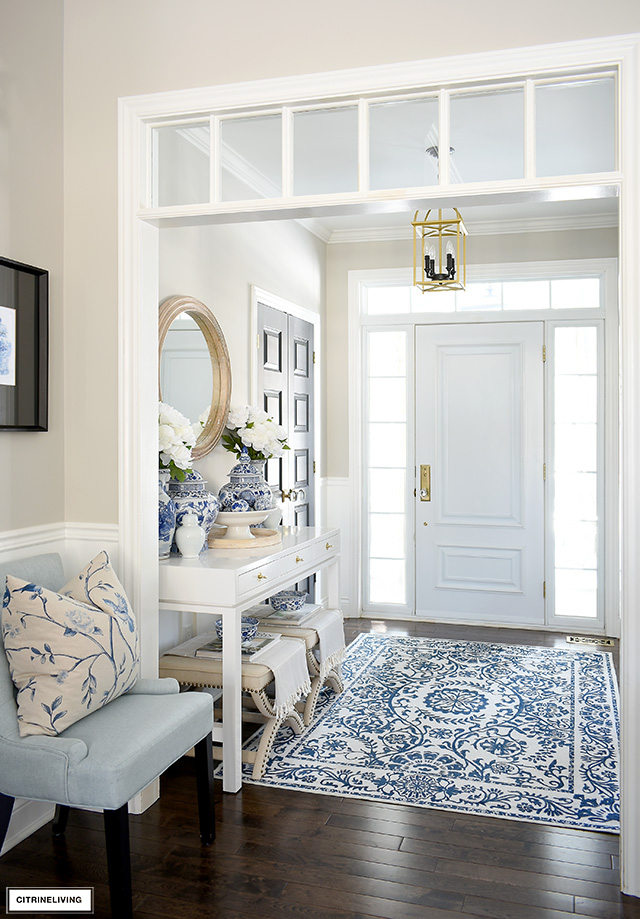 Bright and chic entryway decorate for spring with blue and white rug and accessories, and wood and natural accents.