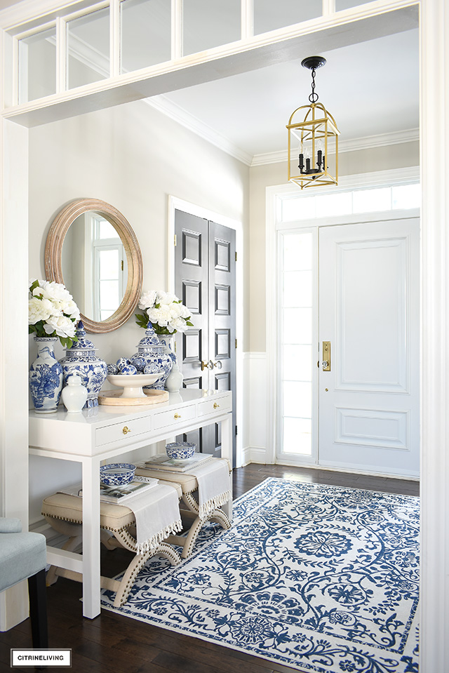 Entryway decorated for spring with blue and white rug, chinoiserie ceramic ginger jars, faux florals and wood touches.