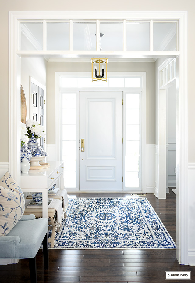 A bright and chic entryway decorated for spring with blue and white.