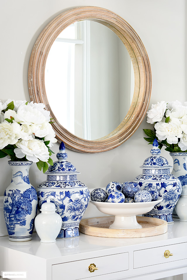 A pretty spring vignette with blue and white chinoiserie vases and jars, faux peonies and a round wood mirror.