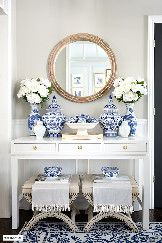 A chic spring-styled console table styled with blue and white ginger jars, vases and faux peonies, accented with a wood mirror and x-base stools underneath.