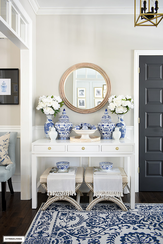 White console table with a round wooden mirror, styled with blue and white ginger jars and vases and faux florals.