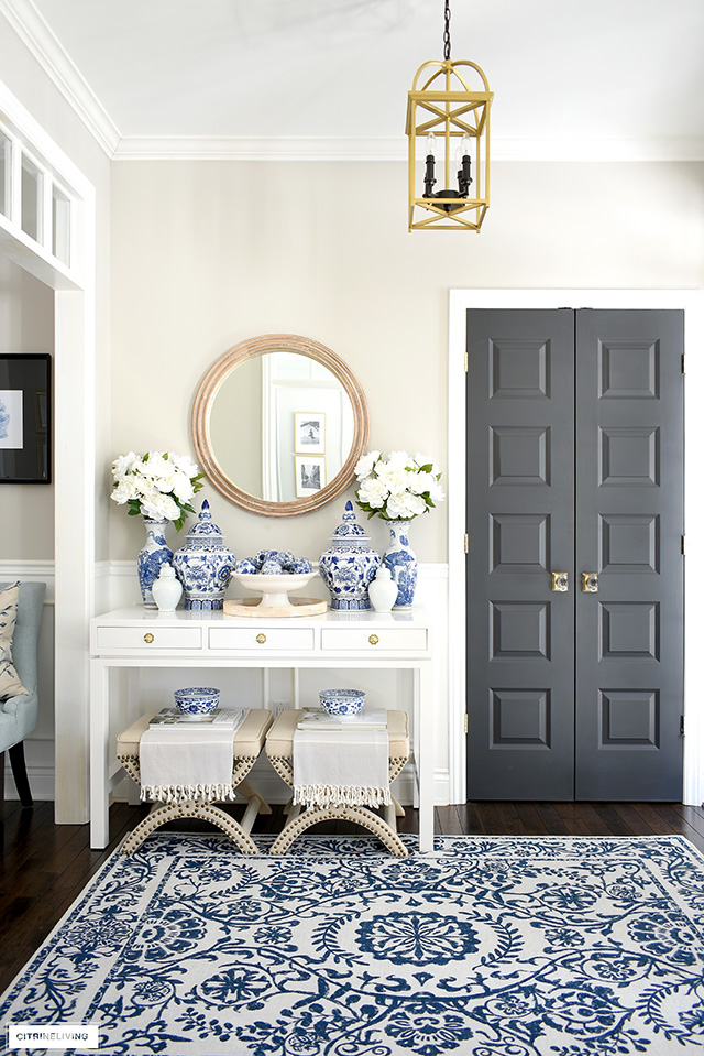 Elegant entryway decor for spring with blue and white rug, ginger jars, peonies and wood touches.