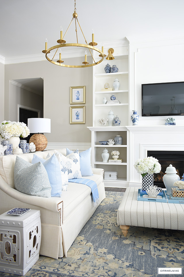 Spring living room decor with blue and white chinoiserie, light blue and cream pillows and accents, natural touches and faux florals.