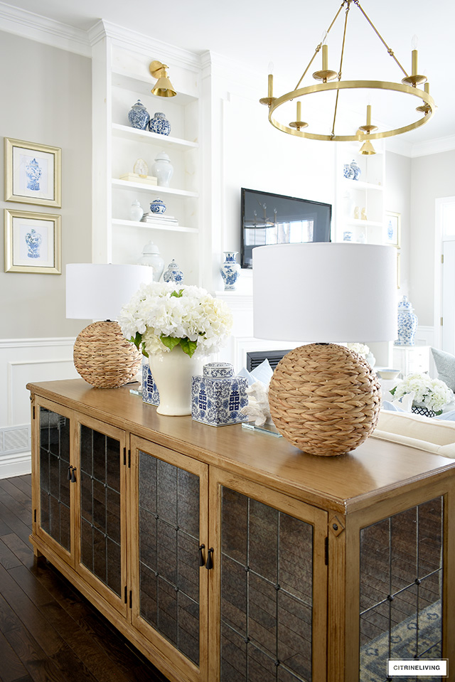 Living room decor for sprig with woven lamps, ginger jars and faux hydrangeas.
