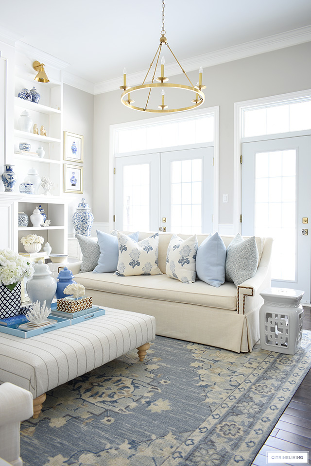 Spring living room decor in pretty blues, creamy whites, floral and geometric print pillows and chinoiserie touches.