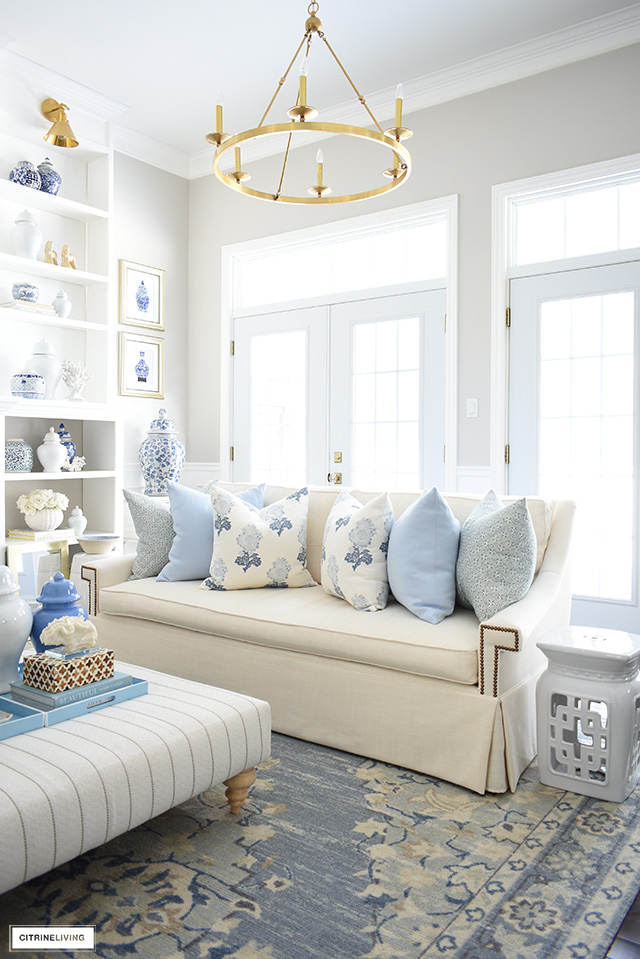 Gorgeous spring living room decor light blue tribal rug, white sofa, blue and white accents and coastal details.