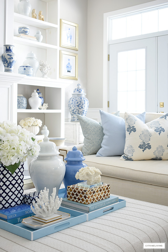 Spring living room decorating - coffee table styled with light blue trays, decorating books, decorative boxes, ginger jars and coral sculptures and faux hydrangeas.