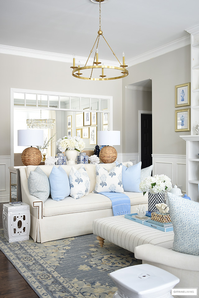 Spring living room decor - soft blue and floral pillows, soft blue tribal print rug, woven and natural touches and chinoiserie are casual, chic and livable.
