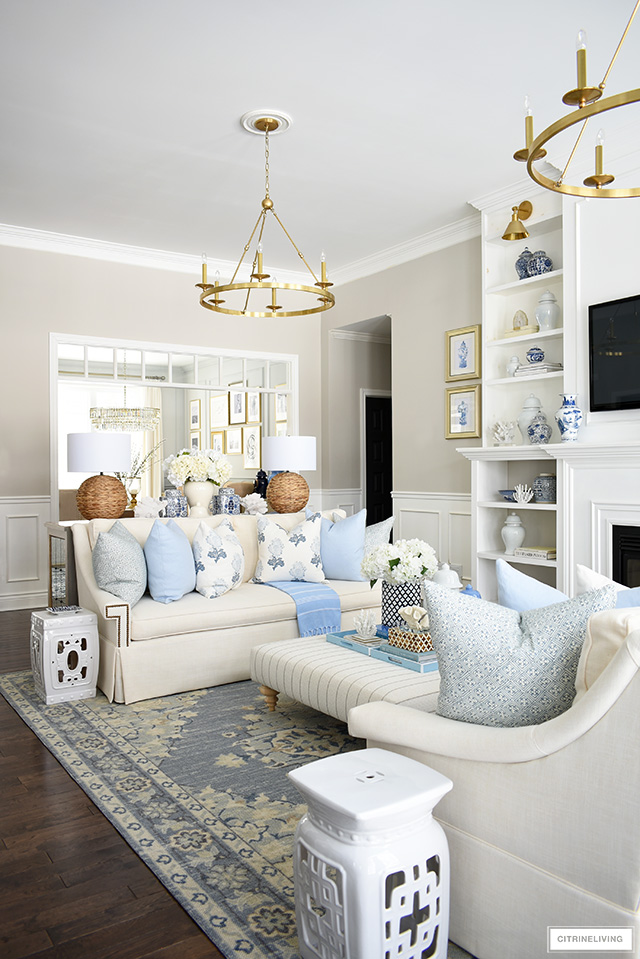 Living room decorating for spring - a beautiful color palette with soft blues and warm whites accented with coastal and natural touches, ginger jars and faux florals.