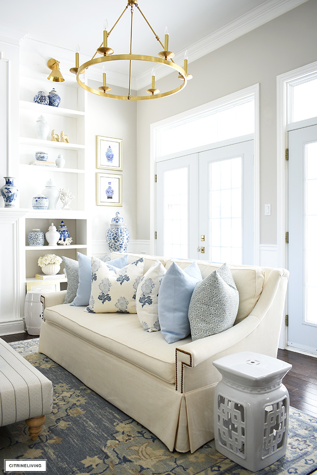 Spring living room decor with gorgeous soft blues, creamy whites, floral and geometric pillows, a light blue rug, and blue and white chinoiserie.
