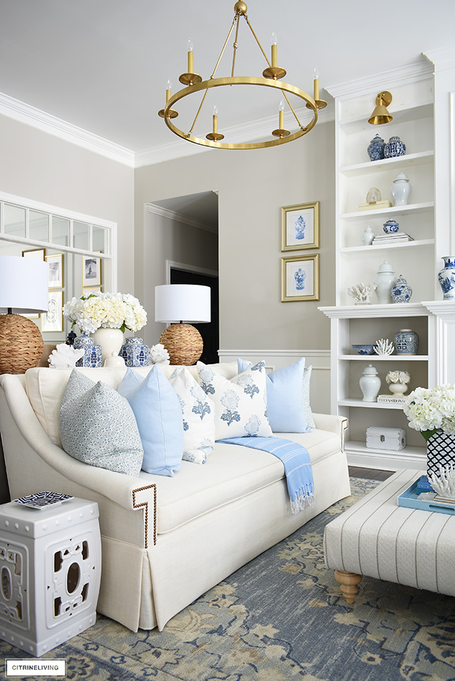 Beautiful spring living room decor with elegant throw pillows in soft blue and white floral and geometric patterns, bookshelves with ginger jars and coral accents and a gorgeous light blue tribal style rug.