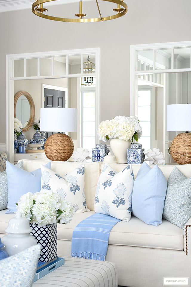 Spring living room decor with beautiful throw pillows in soft blue and white, woven lamps, ginger jars and white florals.