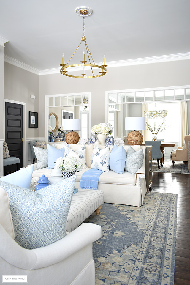 Spring living room decorating with beautiful blue and white pillows, rug, natural and woven touches and coastal accents.
