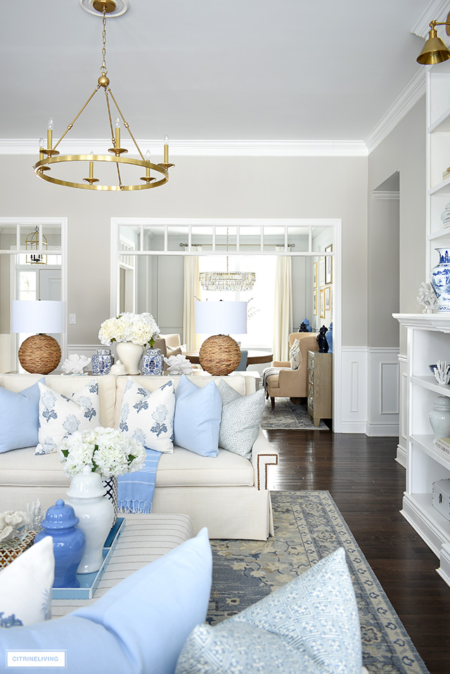 Living room decorated for spring with layers of light blue, creamy white, woven lamps and chinoiserie accents.