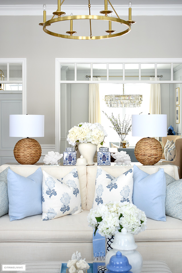 Elegant spring living room decor with woven lamps, blue and white accents and throw pillows.
