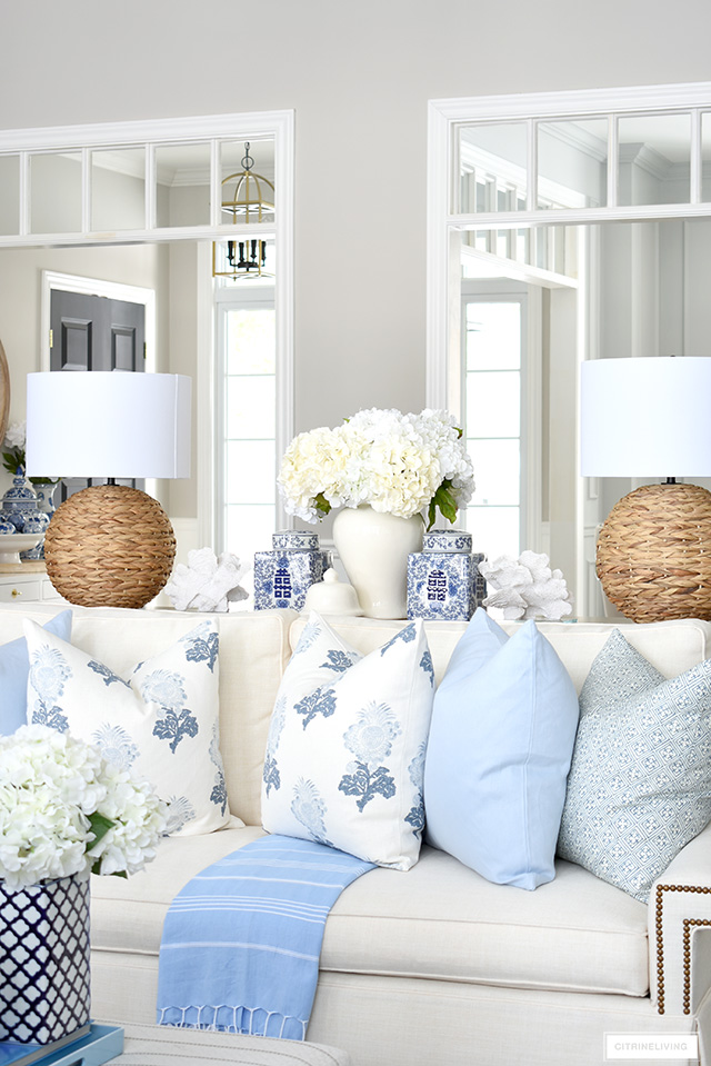 Spring living room decor with beautiful throw pillows in soft blue and white, woven lamps, ginger jars and white florals is elegant and chic.