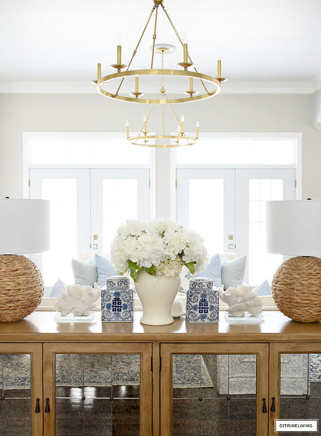 Spring living room decor with woven lamps, blue and white ginger jars, coral accents.